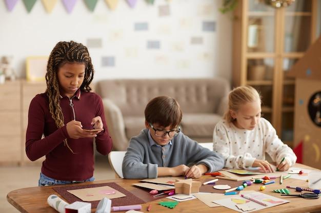 Taille hoch porträt des jugendlichen afroamerikanischen mädchens, das foto des handgemachten bildes macht, um auf sozialen medien während des kunstunterrichts zu kopieren, raum zu kopieren