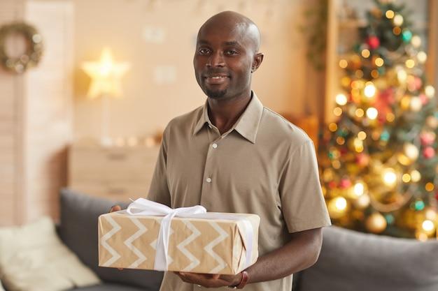 Taille hoch porträt des lächelnden afroamerikanischen mannes, der weihnachtsgeschenk hält, während im gemütlichen hauptinnenraum, kopienraum aufwirft