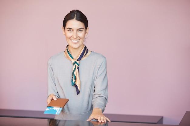 Taille hoch porträt des lächelnden flugbegleiters hinter dem check-in-schalter, der dem passagier tickets übergibt,