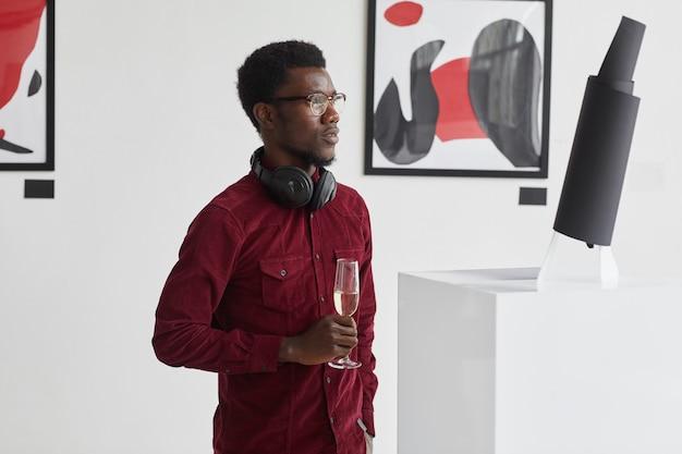 Taille hoch porträt des modernen afroamerikanischen mannes, der champagnerglas hält, während die ausstellung der modernen kunstgalerie erkundet,