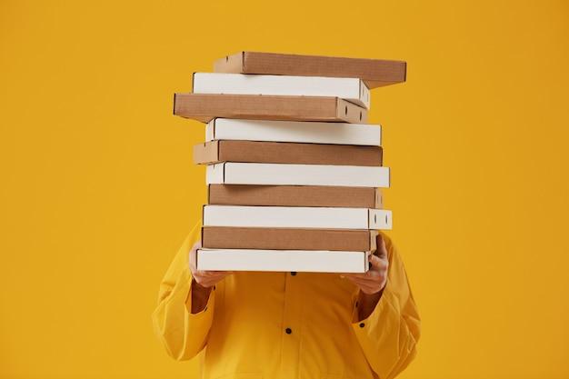 Taille hoch porträt des nicht erkennbaren lieferers, der sich hinter pizzaschachteln versteckt