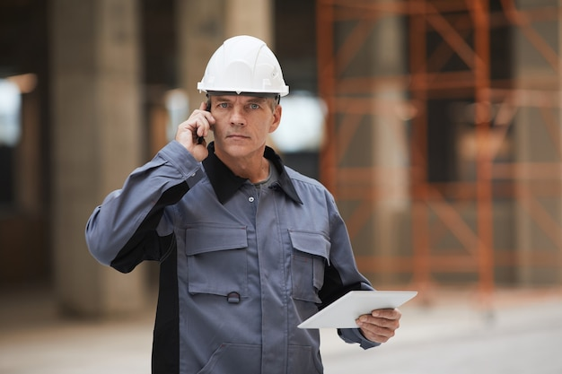 Taille hoch porträt des reifen arbeiters, der per smartphone spricht und auf der baustelle oder in der industriewerkstatt steht,