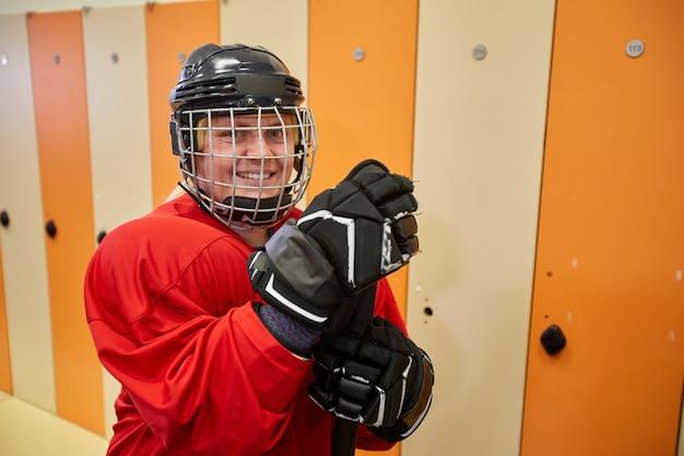 Taille hoch porträt des weiblichen hockeyspielers, der volles ausrüstungslächeln trägt