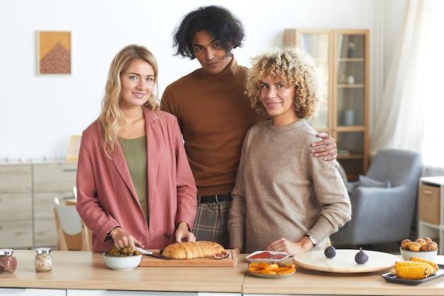 Taille hoch porträt von drei freunden beim kochen für dinnerparty drinnen,