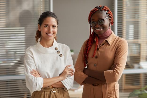 Taille hoch porträt von zwei erfolgreichen jungen geschäftsfrauen, die an der kamera lächeln, während sie souverän stehend mit verschränkten armen im büro posieren, raum kopieren