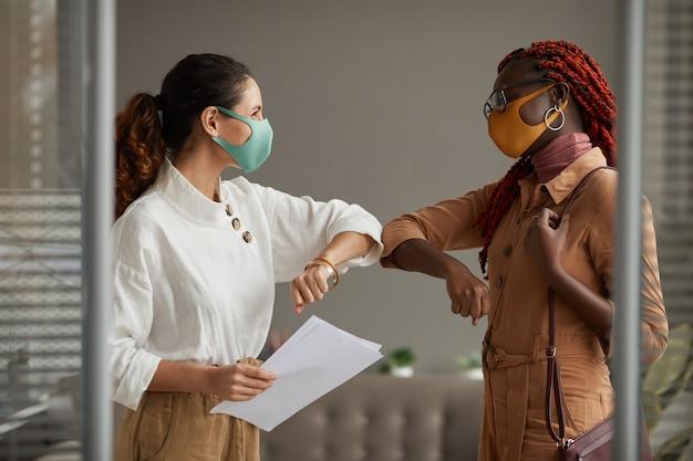 Taille hoch porträt von zwei fröhlichen geschäftsfrauen, die masken tragen und ellbogen als kontaktlose begrüßung im büro stoßen