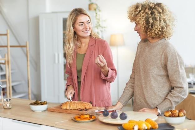 Taille hoch porträt von zwei jungen frauen, die glücklich plaudern, während sie für dinnerparty drinnen kochen,