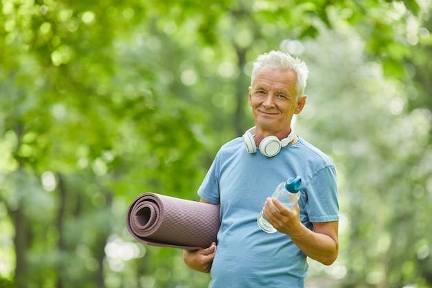 Taille hoch porträtaufnahme des aktiven älteren mannes, der yogamatte und flasche wasser betrachtet kamera betrachtet