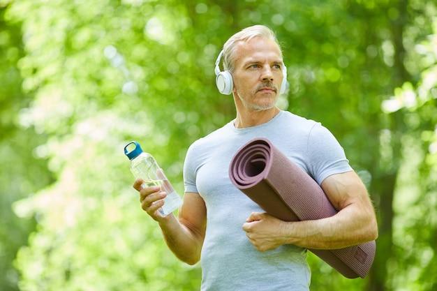 Taille hoch porträtaufnahme des hübschen reifen mannes mit dem muskulösen körper, der matte, flasche wasser wegschaut