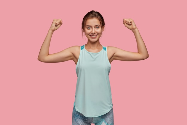 Taille hoch schuss der sportlichen frau hebt die hand, um ihre muskeln zu zeigen