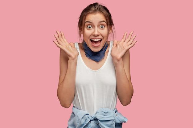 Taille hoch schuss von freudigen teenager umklammert hände in der nähe von gesicht mit glück, hat positiven ausdruck, gekleidet in lässigen t-shirt