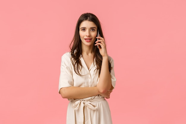 Taille porträt ernsthafte und wunderschöne freche junge frau im kleid, telefon halten, am telefon sprechen, freund anrufen, gespräch führen, mit bestellung prüfen, rosa wand stehen