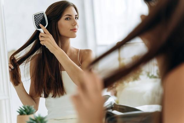 Taillen-hochformat der glücklichen hübschen frau in häuslicher kleidung, die ihr haar vor dem spiegel kämmt, während sie eine große bürste hält. stock foto