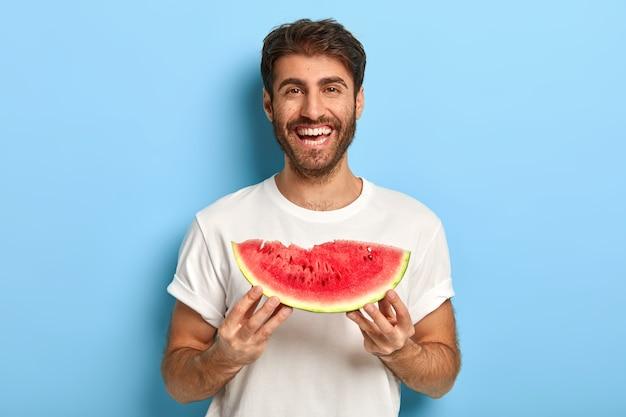 Taillenaufnahme des lächelnden mannes an einem sommertag, der eine scheibe wassermelone hält