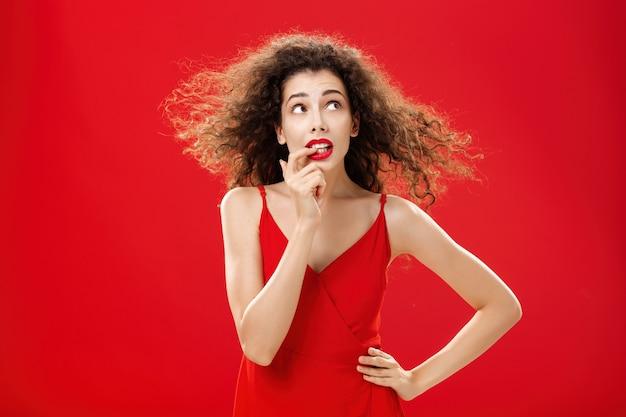 Taillenaufnahme einer besorgten und besorgten, unsicheren, süßen frau mit lockiger frisur im roten abendkleid, die in den finger beißt und in der oberen rechten ecke mit der hand auf der taille beunruhigt oder befragt aussieht. platz kopieren