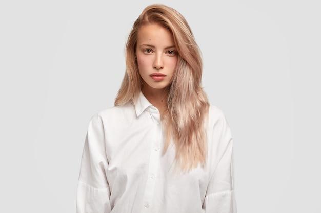 Taillenaufnahme einer ernsthaften kaukasischen frau mit geraden luxuriösen haarmodellen im studio