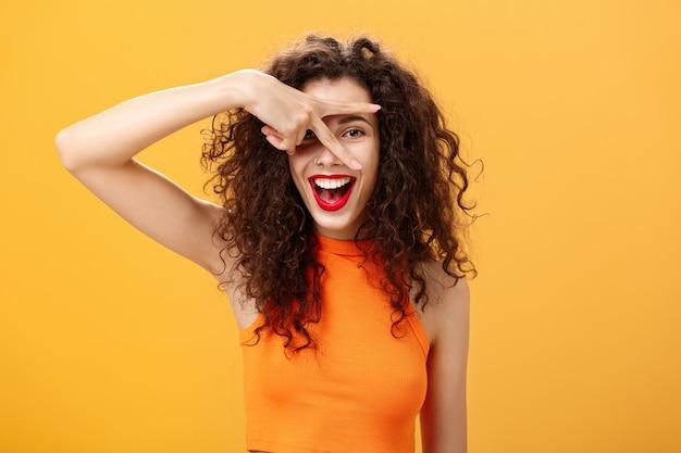 Taillenaufnahme einer kreativen, fröhlichen kaukasischen frau mit lockiger frisur und kleiner tätowierung, die friedensgeste zeigt und durch die finger in die kamera späht, die glücklich lächelt und spaß über orangefarbener wand hat.