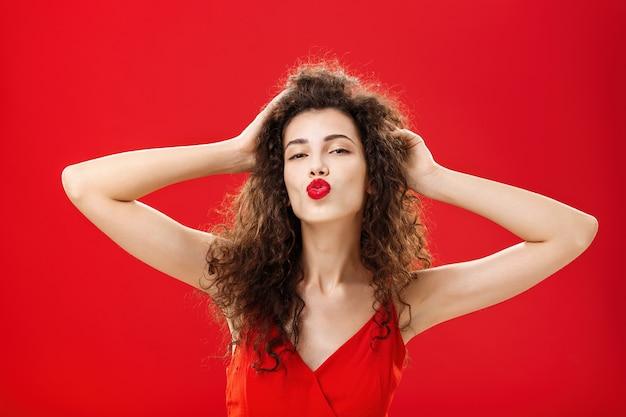 Taillenaufnahme einer selbstbewussten, flirtenden und eleganten jungen reichen frau mit lockiger frisur in rotem lippenstift und abendkleid, die die haare berührt, die lippen in mwah falten, die dem bewunderer einen kuss geben, der sich selbstbewusst fühlt.