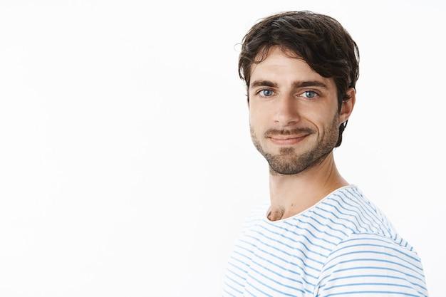 Taillenaufnahme eines optimistischen, selbstbewussten und optimistischen, energiegeladenen jungen unternehmers, der ein neues online-geschäft gründet und sich glücklich und enthusiastisch lächelt, im profil steht und sich nach vorne dreht