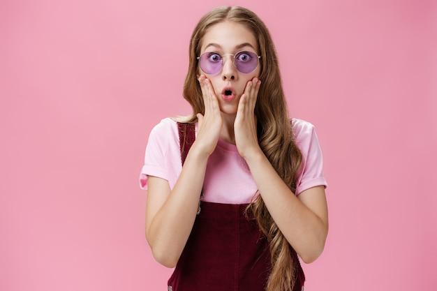 Taillenaufnahme eines sylischen jungen mädchens mit tätowierung und gewellter, hübscher natürlicher frisur, die vor erstaunen die handflächen an die wangen drückt und die lippen mit schockfalten überrascht, als sie die kamera über der rosafarbenen wand anstarrten.