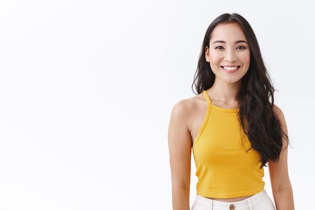 Taillenbegeisterte asiatische frau mit langen dunklen haaren, gelbes trendiges oberteil, lächelnd mit freundlichem, unbeschwertem ausdruck als schauende kamera, positive, freudige emotionen ausdrücken, weißer hintergrund