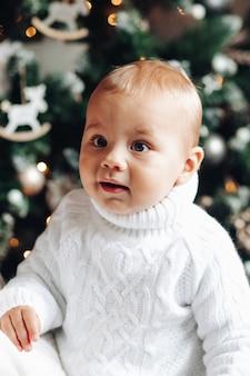Taillenfoto eines entzückenden kindes im gestrickten weißen pullover mit weihnachtsbaum