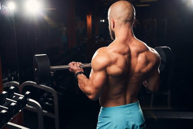Taillenfoto eines starken sportlers, der gewichte hebt, um seinen rücken im fitnessstudio zu trainieren
