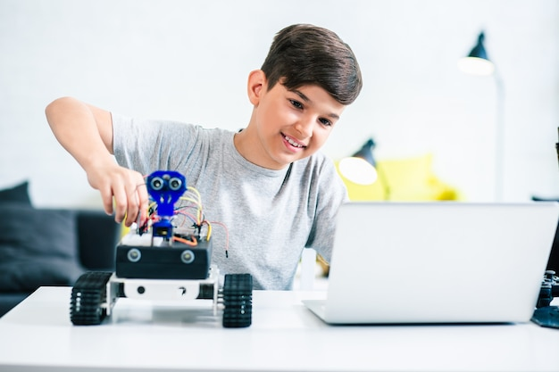 Taillenhöhe eines positiven kleinen jungen, der am tisch sitzt und zu hause einen modernen roboter baut