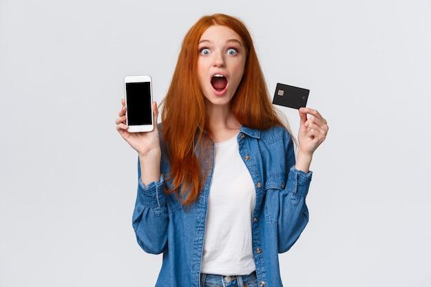 Taillenporträt aufgeregt, erstaunt und begeistert rothaarige studentin, die kreditkarte hält