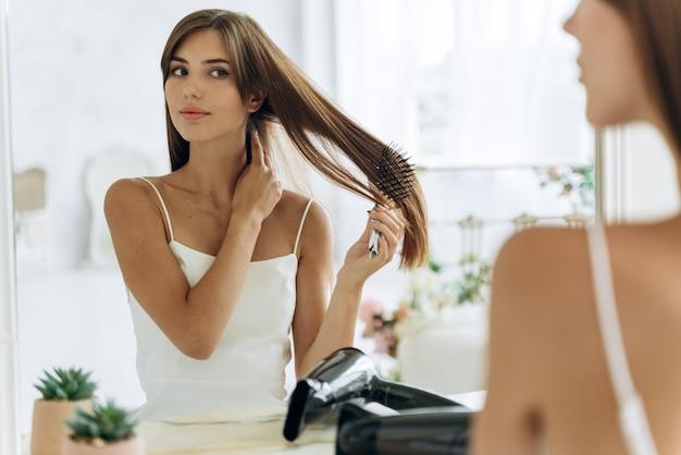 Taillenporträt der frau, die sich im spiegel widerspiegelt, die tägliche routine macht, während sie die haarbürste hält, um ihr haar zu säubern. weibliches schauen und verworrenes haar. beauty-behandlungskonzept