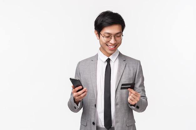 Taillenporträt des glücklichen, gutaussehenden asiatischen männlichen unternehmers, des büroangestellten im anzug, der kreditkarte und des mobiltelefons hält, lächelnd, leicht für online-kauf unter verwendung des bargeldlosen zahlungsinternets zahlend