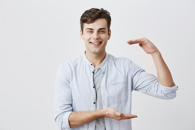 Taillenporträt des kaukasischen männlichen modells, das freudig mit weißen zähnen lächelt und größe der schachtel mit geschenk für seine freundin demonstriert, aktiv gestikulierend. körpersprache