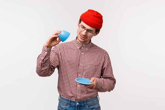 Taillenporträt des lustigen europäischen mannes mit schnurrbart in der hipster-mütze, gläser, sehen traurig aus, als kein kaffee mehr übrig ist, schauen düster auf leere tasse, wollen diesen köstlichen tee noch etwas trinken,