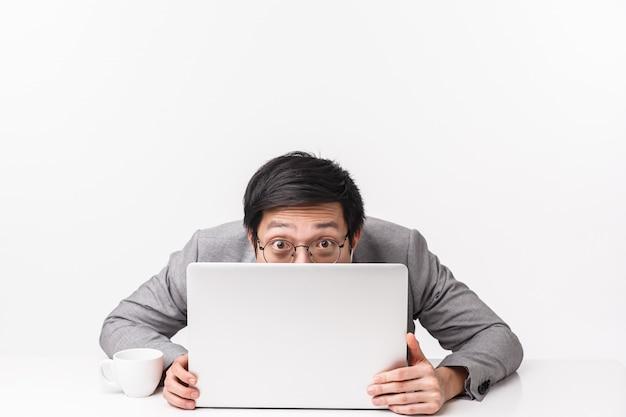 Taillenporträt des lustigen und albernen hübschen asiatischen büroangestellten, mann im anzug, der am tisch sitzt und gesicht hinter geöffnetem laptop versteckt, späht, arbeit vermeidet und herumalbern, auf einer weißen wand