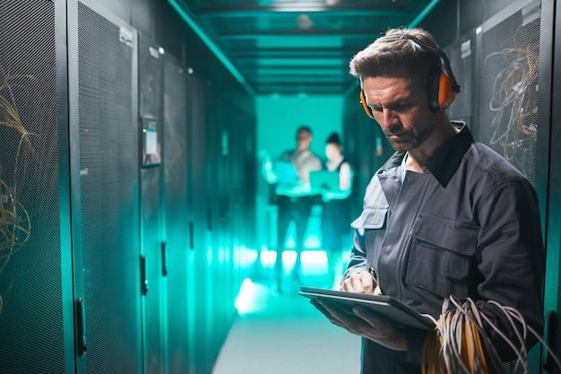 Taillenporträt des netzwerkingenieurs mit tablet im serverraum während der wartungsarbeiten im rechenzentrum, platz kopieren
