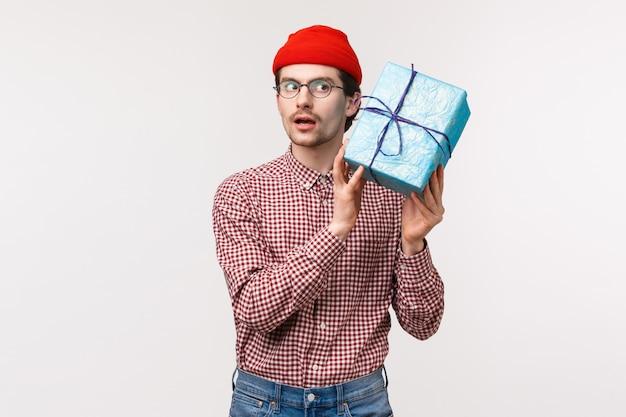 Taillenporträt des neugierigen lustigen kaukasischen bärtigen mannes in der roten mütze, in den gläsern, die geschenkbox nahe ohr schütteln, als erraten, was drinnen ist, schauen konzentriert, wollen überraschung öffnen und gegenwart sehen