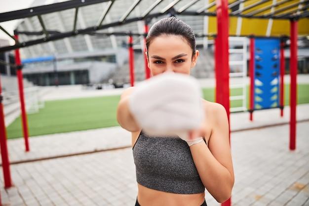 Taillenporträt einer athletischen jungen frau in boxbandagen, die einen kreuzschlag auf die kamera zeigt