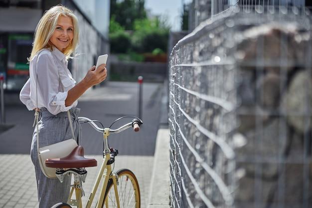 Taillenporträt einer fröhlichen, fröhlichen frau in weißer bluse, die handy hält, während sie mit dem fahrrad in der stadt spazieren geht