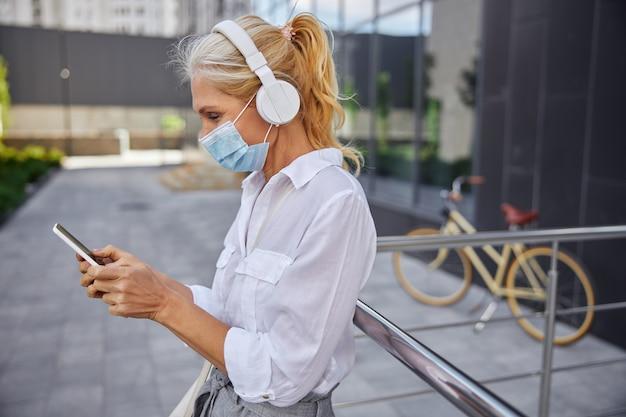 Taillenporträt einer geschäftsfrau im weißen hemd mit schutzmaske, während sie musik in den kopfhörern hören