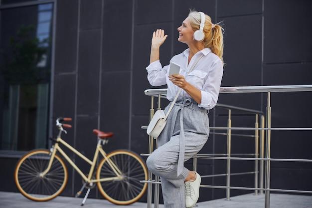Taillenporträt einer glücklich lächelnden blonden frau, die mit dem handy spricht, während sie im freien vor einem modernen gebäude steht