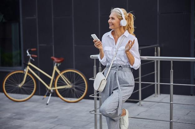 Taillenporträt einer hübschen dame, die mit freunden auf dem handy spricht, während sie vor einem modernen gebäude und einem retro-fahrrad steht