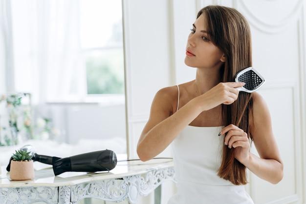 Taillenporträt einer strahlenden dame, die ihr langes dunkles haar kämmt, während sie mit ruhigem lächeln wegschaut. konzept zur haarpflege. stock foto