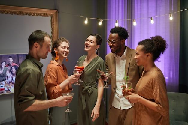 Taillenporträt einer verschiedenen gruppe von freunden, die lachen und plaudern, während sie die party zu hause genießen