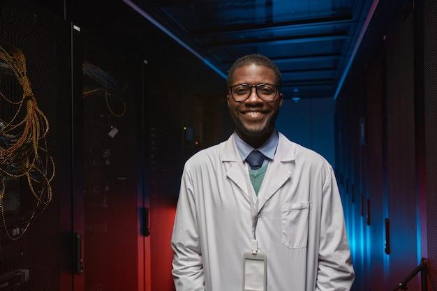 Taillenporträt eines afroamerikanischen datenwissenschaftlers, der laborkittel trägt und in die kamera lächelt, während er mit supercomputer im serverraum arbeitet, kopierraum