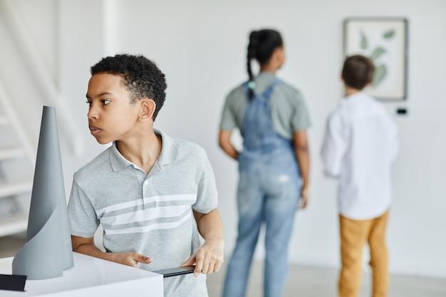 Taillenporträt eines afroamerikanischen jungen, der skulpturen in der galerie für moderne kunst betrachtet, platz kopieren