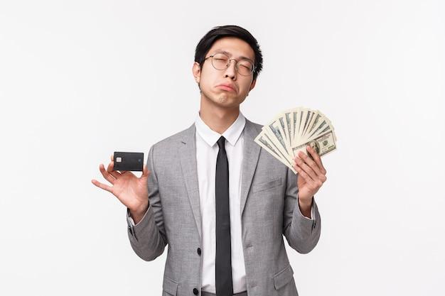 Taillenporträt eines gelangweilten und widerstrebenden jungen reichen asiatischen mannes im grauen anzug
