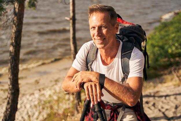 Taillenporträt eines glücklichen athletischen mannes, der mit stöcken und rucksack auf dem weg in der nähe des sees nordic walking geht