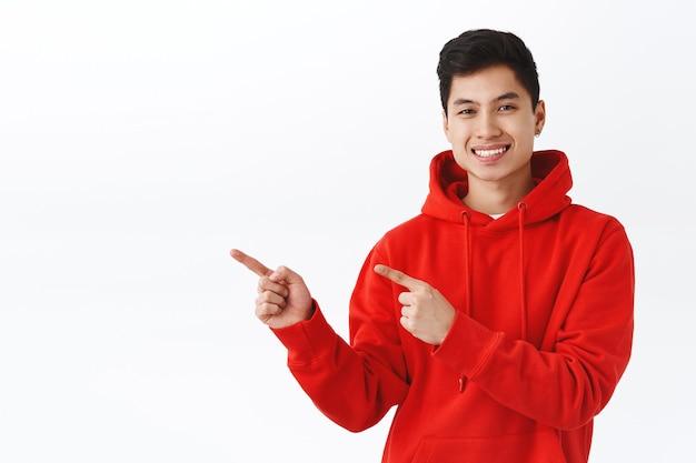 Taillenporträt eines gutaussehenden asiatischen mannes im roten hoodie gibt ratschläge, wo man gute gesellschaft findet, um einen job zu bekommen
