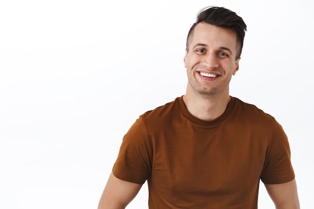 Taillenporträt eines gutaussehenden, freundlich aussehenden, freundlichen mannes, der etwas angenehmes und entzückendes anlächelt
