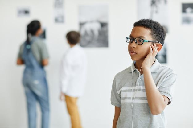 Taillenporträt eines jungen afroamerikanischen jungen, der gemälde in der galerie für moderne kunst betrachtet, platz kopieren